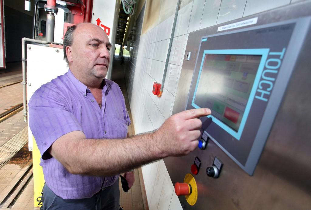 Ein Mitarbeiter wählt das Waschprogramm für die Bahn aus.